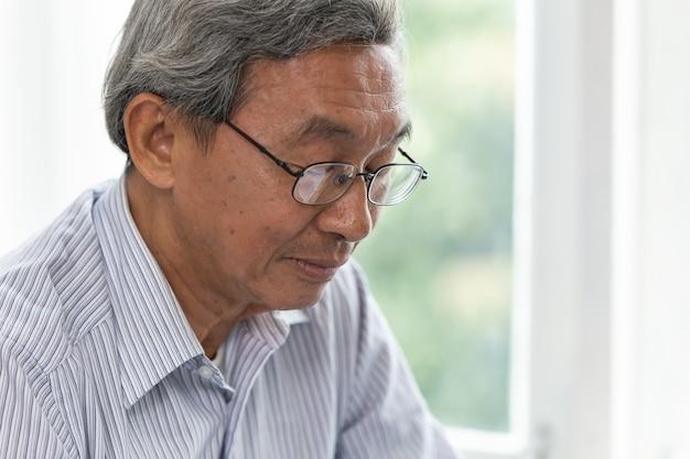 Close-up ouderling blij gezicht vreedzame rustige slimme blik met glazen aziatische oude man.