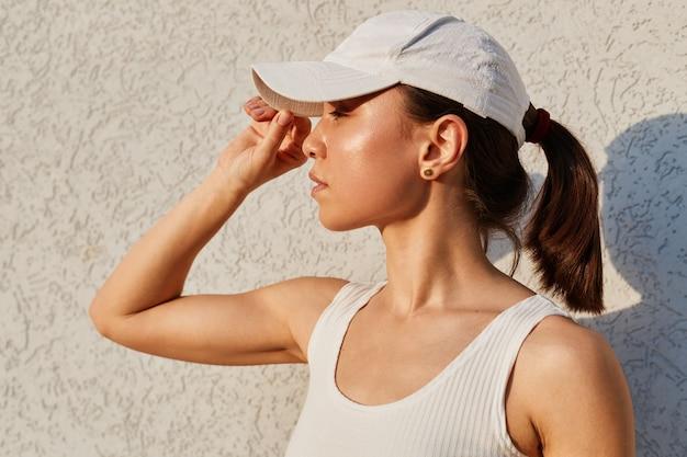 Close-up outdoor portret van slanke, verbijsterde vrouw met witte top en vizierdop, wegkijkend, gefotografeerd tijdens sportoefeningen, training, gezonde levensstijl.