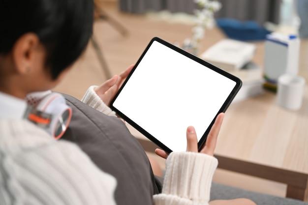Close-up over schouder zicht van jonge vrouw die digitale tablet gebruikt terwijl ze op de bank zit.