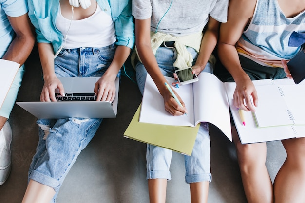 Close-up overhead portret van meisje in blauw shirt en spijkerbroek met laptop op knieën zittend naast universiteitsgenoten. vrouwelijke student die lezing in notitieboekje schrijft en telefoon tussen vrienden gebruikt.