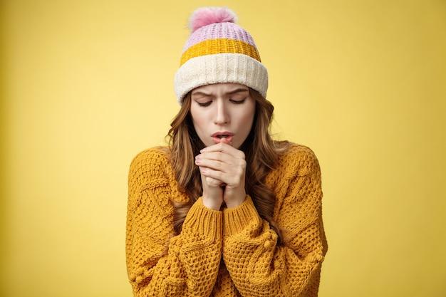 Close-up overstuur ongemakkelijke schattige tedere jonge blanke vrouw die warme lucht ademt handen opwarmen ijskoud buiten bukkend bevend met lichte kleding, staande gele achtergrond