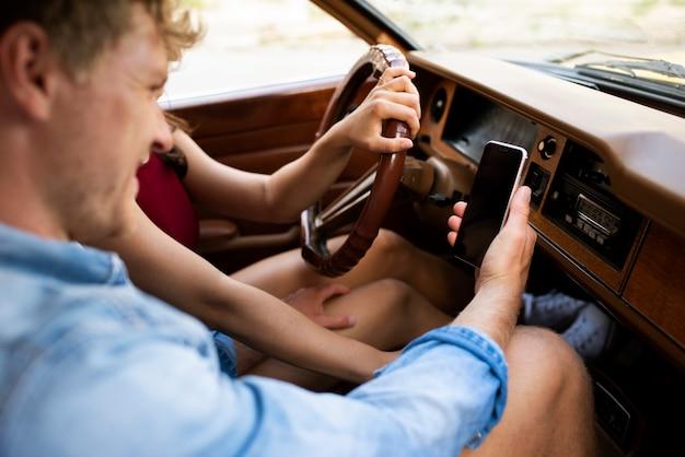 Close-up paar in auto met smartphone