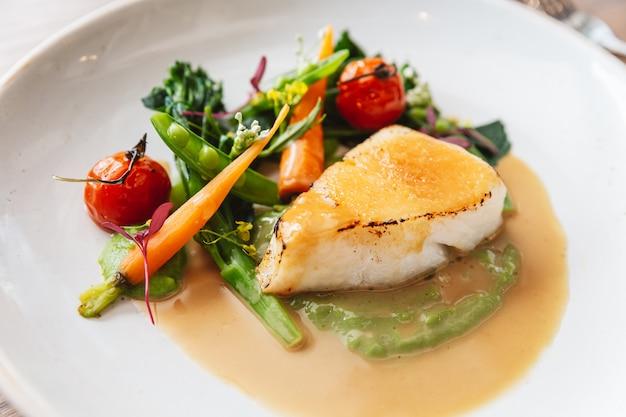 Close-up pan aangebraden kabeljauw visfilet met tomaat, bonen en wortel in jus saus. geserveerd in een wit bord met een zilveren mes en vork.