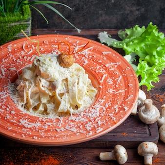 Close-up pasta met saus, parmezaanse kaas, champignons, sla op een donkere houten tafel