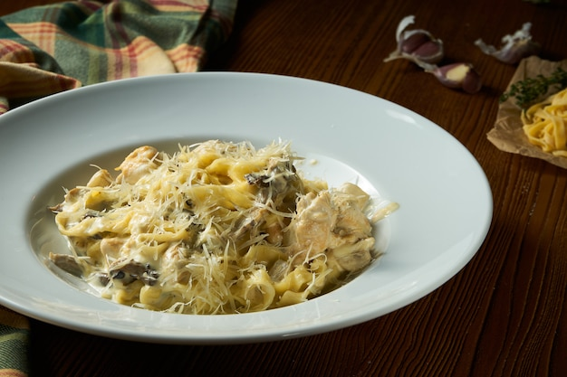 Close-up pasta met wilde paddestoelen, witte saus, parmezaanse kaas in witte kom op houten achtergrond.