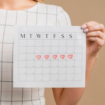 Close-up periode kalender met getekende hartvormen