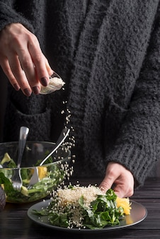 Close-up persoon kruiden salade met zout