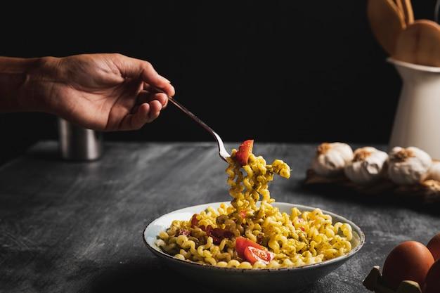 Close-up persoon met vork en pasta