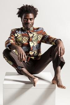 Close-up pfoto van wanhoop afrikaanse man camera kijken. binnen, geïsoleerd op grijze achtergrond