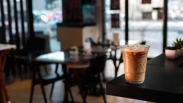 Close-up plastic kopje ijskoffie met melk op tafel