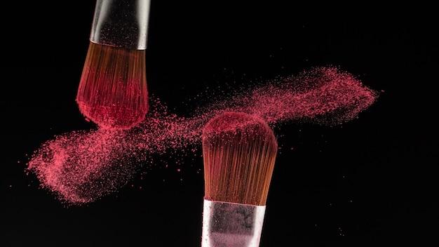 Close-up poeder splash en borstel voor make-up artist of beauty blogger op zwarte achtergrond