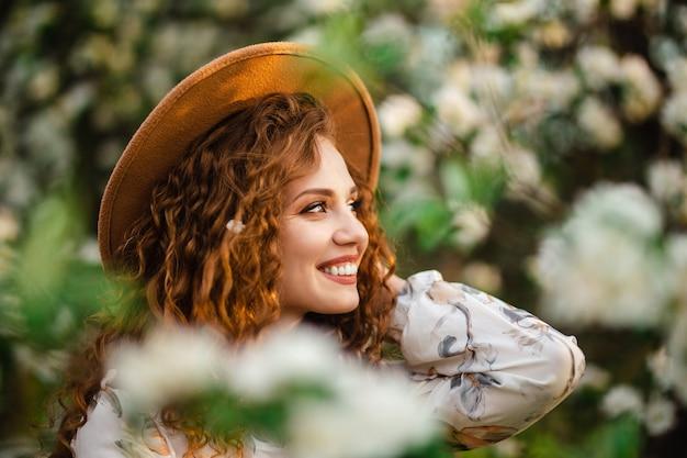 Close-up portarit van een jong meisje dat lacht en plezier heeft onder de bloeiende bomen in de lente een een stralende dag in het park. vrouw met krullend donkerbruin haar in een beige hoed en witte jurk geniet van mooi weer