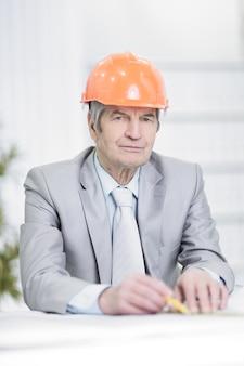 Close-up .portrait van een senior ingenieur zit aan zijn bureau