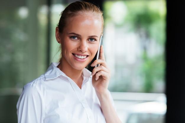 Close-up portret als een glimlachende zakenvrouw aan de telefoon praat en naar de camera kijkt