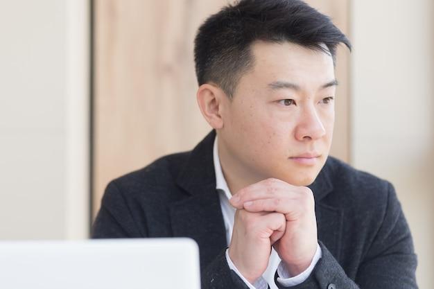 Close-up portret aziatische peinzende jonge kantoor werknemer man op de werkplek. geconfronteerd met een serieuze mannelijke business manager in formeel pak denken over het oplossen van een probleem. zakenman aan bureau met computer of laptop