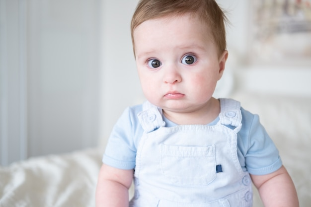 Close-up portret babyjongen 6 maanden oud in blu kleren glimlachend en zittend op wit bed thuis.