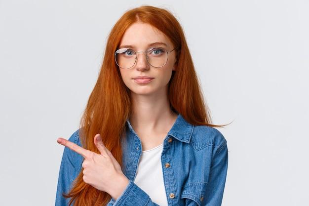 Close-up portret ernstige slimme en vastberaden jonge roodharige vrouw maken van een definitieve definitieve keuze, vinger naar links en camera vertrouwen kijken, permanent wit