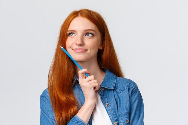 Close-up portret geïnspireerd, dromerige en getalenteerde schattige roodharige vrouw die denkt wat tekenen, kleurpotlood vasthouden en tevreden glimlachen, illustraties weergeven, ontwerpen over wit