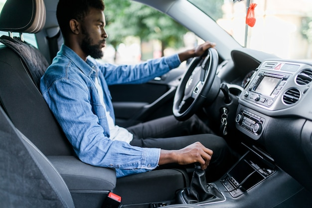 Close-up portret gelukkig lachend jonge afrikaanse man zit in zijn nieuwe auto opgewonden klaar voor reis