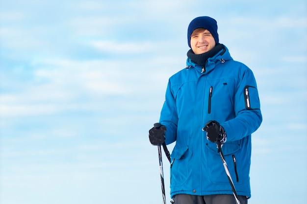 Close-up portret. gelukkige jonge kerel die ski's en stokken in het hele land in zijn handen houdt. de man leidt een gezonde levensstijl, een wintersport.