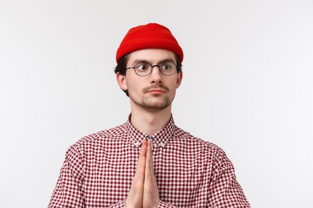 Close-up portret grappige blanke man met snor, rode muts en bril, maak namaste of bid gebaar wegkijken met ernstige vastberaden uitdrukking,