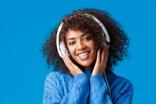 Close-up portret hipster afro-amerikaanse vrouw met krullend kapsel, koptelefoon op en lachend, genietend van muziek, luister naar favoriete liedjes staan blauwe achtergrond