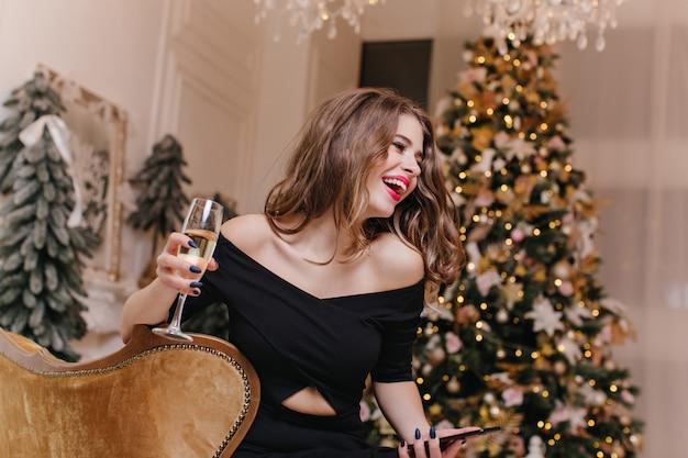 Close-up portret in kamer van jonge slavische model in een mooie kamer met nieuwjaars versieringen. vrouw met donker haar lacht oprecht terwijl ze een glas mousserende witte wijn vasthoudt