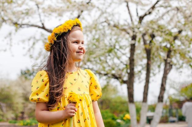 Close-up portret in profiel van een lachend meisje met een krans van gele paardebloemen op haar hoofd en een...