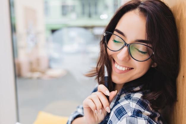 Close-up portret intelligente jonge brunette vrouw in zwarte glazen koelen op venster. comfortabele werkplek, opgewekte sfeer, lachend met gesloten ogen.