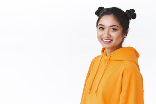 Close-up portret jonge aziatische tienermeisje met schattige twee haarbroodjes, draag oranje hoodie, staande half gedraaid tegen witte muur in de buurt van lege lege ruimte voor reclame