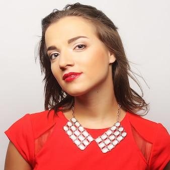 Close-up portret jonge gelukkige vrouw in rode jurk