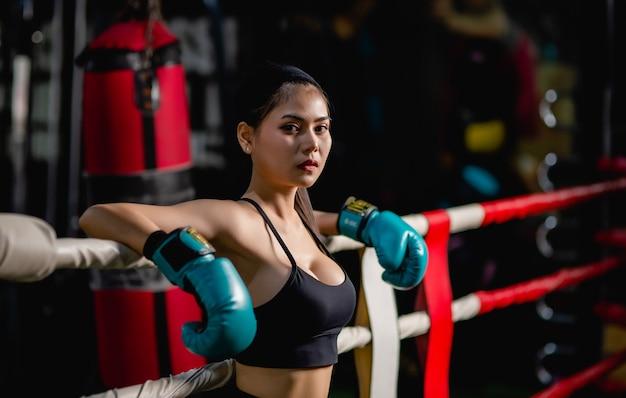 Close-up portret jonge mooie vrouw in bokshandschoen staande op canvas na training met moe, training in fitness gym,