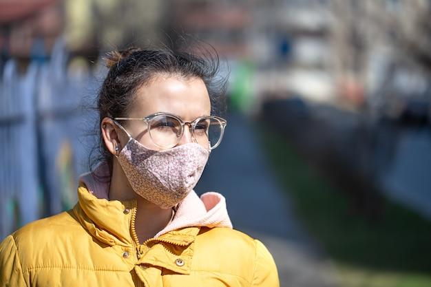 Close-up portret jonge vrouw in een masker tijdens de pandemie. coronavirus (covid-19 . concept van gezondheidszorg tijdens een epidemie of pandemie