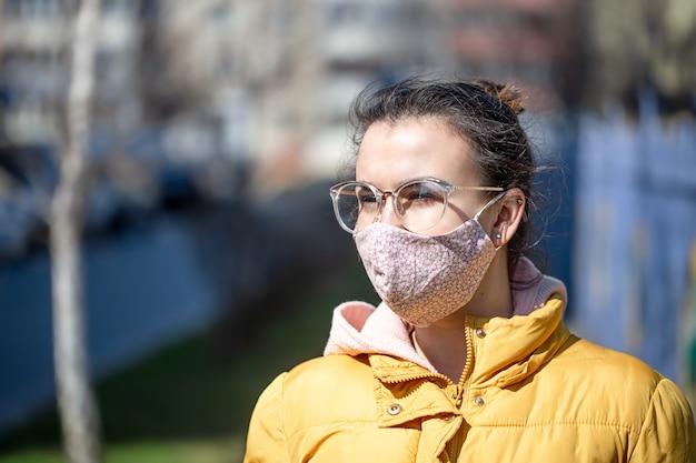 Close-up portret jonge vrouw in een masker tijdens het pandemische coronavirus.