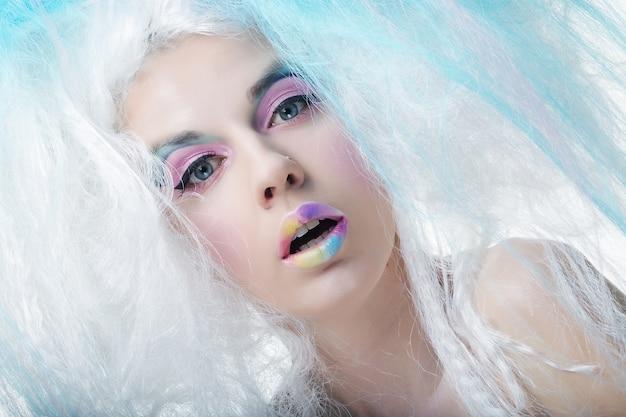 Close-up portret jonge vrouw met lichte make-up en creatief haar