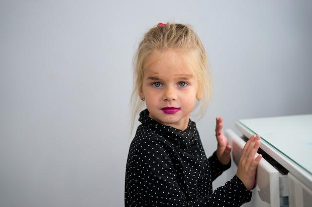 Close-up portret klein blond meisje maakte haar eigen make-up met de cosmetica van haar moeder
