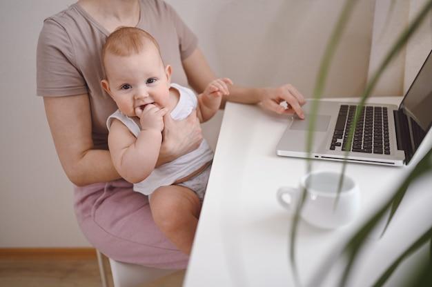 Close-up portret kleine babyjongen grappige gezichtsuitdrukking zittend op moeders schoot studeren laptop