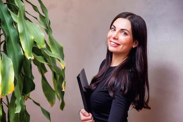 Close-up portret lachende jonge zakenvrouw beheerder op getextureerde grijze muur achtergrond. vrouwelijke manager staat en kijkt naar de camera. haar armen gekruist met map met documenten en glimlachen