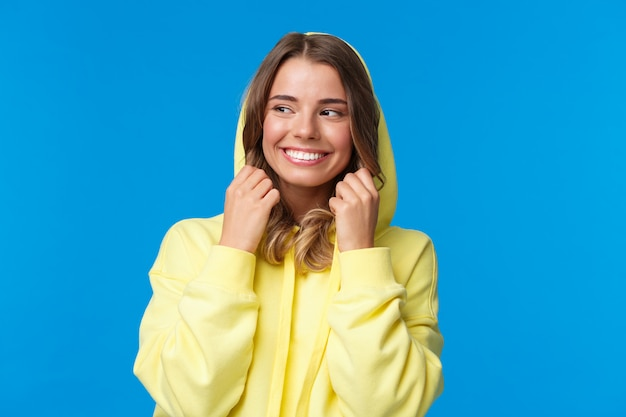 Close-up portret mooi charmant blond meisje op de capuchon van sweatshirt en lachend, kijk weg, voel koud als wandelen op de lentedag, zorgeloos staan