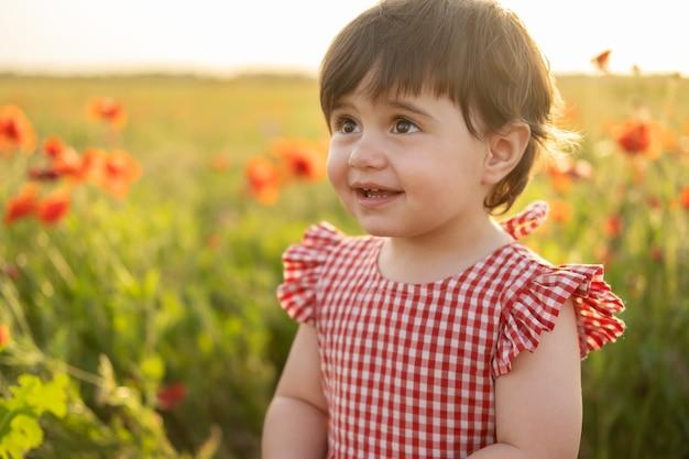 Close-up portret mooi gelukkig babymeisje in rode jurk glimlachend op veld van papavers bij zomer zonsondergang
