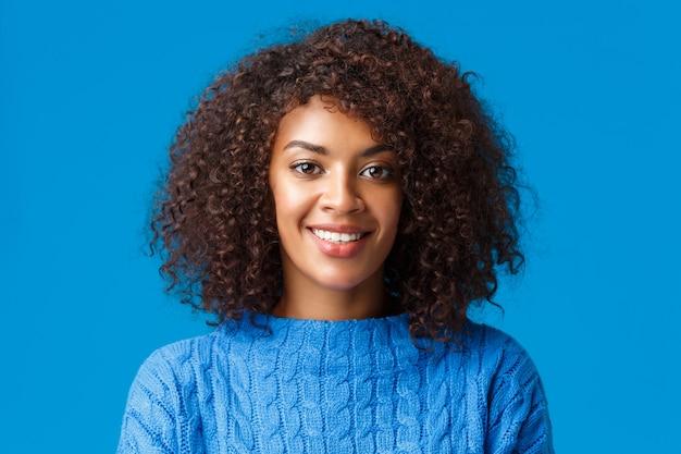 Close-up portret mooie jonge afro-amerikaanse vrouw met krullend, afro kapsel, glimlachend met gelukkige aangename uitdrukking, genieten van wintervakantie, trui dragen, blauwe muur.