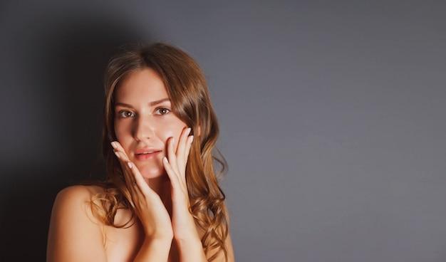 Close-up portret mooie jonge vrouw bang met haar handen op haar gezicht tegen donkere geïsoleerde achtergrond