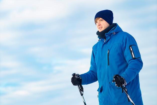 Close-up portret. nadenkend jonge kerel die langlaufski's en stokken in zijn handen houdt. de man leidt een gezonde levensstijl, een wintersport.
