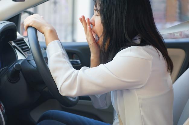 Close-up portret slaperig, geeuw, ogen dicht jonge vrouw rijdt haar auto na een lange uur reis