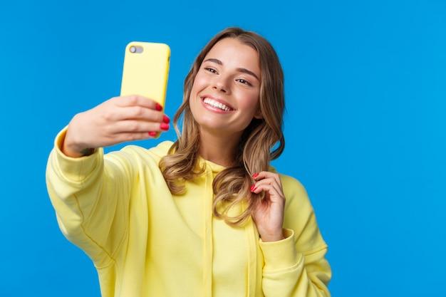 Close-up portret teder schattig blond meisje in gele hoodie, met mobiele telefoon, selfie te nemen met smartphone poseren fotofilter toe te voegen in toepassing, staand