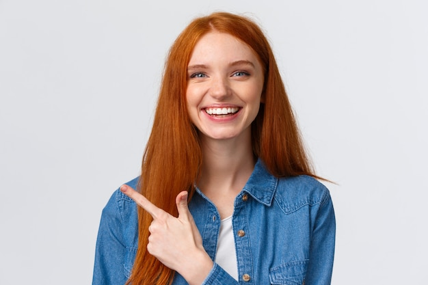 Close-up portret uitgaande knappe vrolijke roodharige tienervrouw in casual outfit, lachend en pratend, recente gebeurtenis bespreekend, wijzende vinger naar banner, reclame aanbevelen