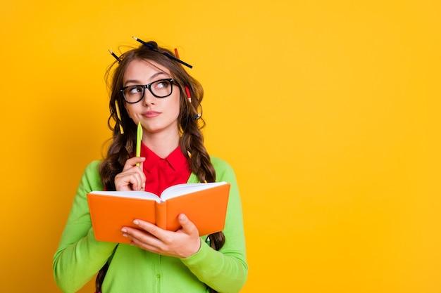 Close-up portret van aantrekkelijk bedacht intelligent geniaal meisje dat essay schrijft dat een oplossing creëert die over een felgele kleurachtergrond wordt geïsoleerd