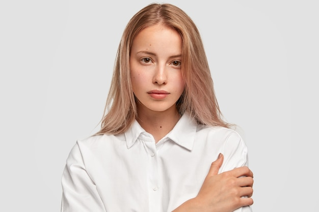 Close-up portret van aantrekkelijk europees vrouwelijk model houdt de handen gekruist en kijkt met zekere uitdrukking rechtstreeks in de camera