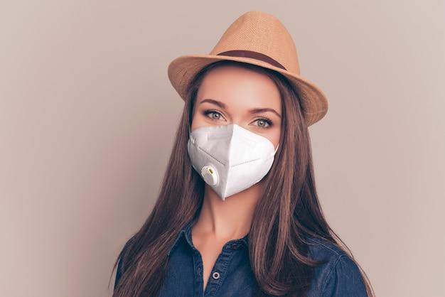 Close-up portret van aantrekkelijk gezond meisje met n95 wit beademingsmasker 2019 china wuhan ncov mers influenza veiligheidspreventie geïsoleerd op beige kleur achtergrond