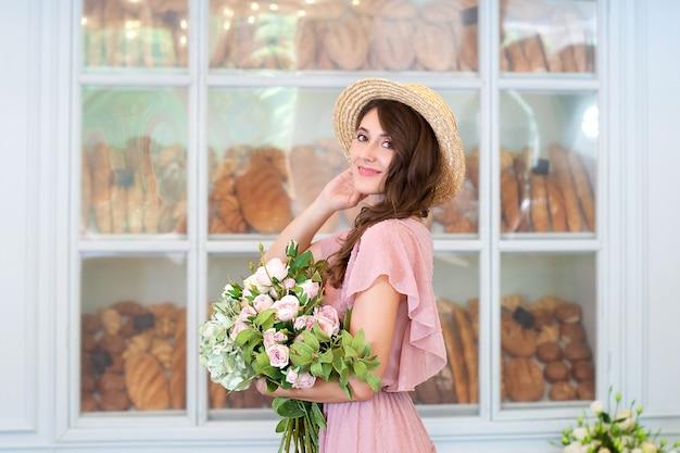 Close-up portret van aantrekkelijk jong meisje in jurk en strohoed met een boeket bloemen